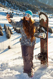 Girl snowboarder standing on a mountain top at sunset and making a selfie Stock Photography