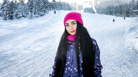 Girl snowboarder standing in winter on the ski slope smiling and looking Stock Photo
