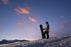 Girl snowboarder stands on a hillside against  dark sunset sky. Girl snowboarder stands on a hillside against the dark sunset sky Stock Photography
