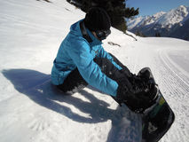 Girl snowboarding. Girl tying the boot to the snowboard Stock Photography