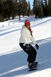 Girl snowboarding. A snowboarding young woman having fun on a slope Royalty Free Stock Photography
