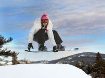 Girl snowboarding. Young mexican girl jumping on a snowboard Stock Image