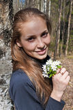 The girl with the snowdrops. Smiling girl holding a bouquet of snowdrops sunny spring day Royalty Free Stock Photography
