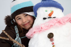Girl with snowman Royalty Free Stock Image