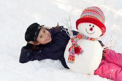 Girl with snowman. Fun outside in winter time Royalty Free Stock Photography