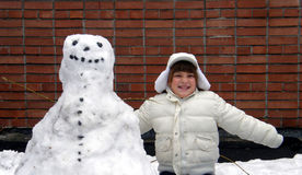Girl and snowman. Smiling girl in white and snowman Royalty Free Stock Photos