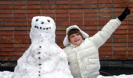Girl and snowman. Smiling girl in white and snowman Royalty Free Stock Image