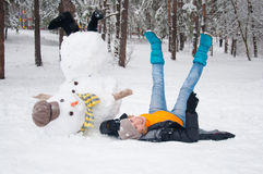 The girl with a snowman. Amusing woman poses with the turned snowman Royalty Free Stock Images