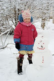 Girl with a snowman outdoor Stock Images
