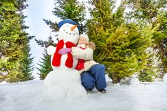 Girl and snowman with scarf together in forest Royalty Free Stock Photo