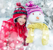 Girl and snowman. Smiling little girl and snowman Royalty Free Stock Photos