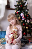 Girl with snowman under a Christmas tree Stock Photography