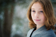 Girl in a snowy forest. Twelve year old girl outdoors in winter in a forest covered in snow Stock Photos
