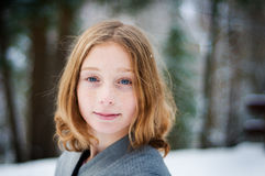 Girl in a snowy forest. Twelve year old girl outdoors in winter in a forest covered in snow Royalty Free Stock Photo