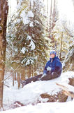 Girl in a snowy forest. Twelve year old girl sitting on a snow covered rock back lit by the sun in a snowy winter forest Stock Photos