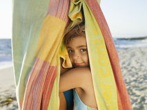 Girl (5-7) snuggling up to mother wrapped in large towel on sandy beach, smiling, close-up, side view, portrait Stock Photo
