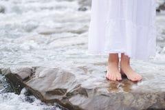 Girl soaking feet in stream Stock Photo
