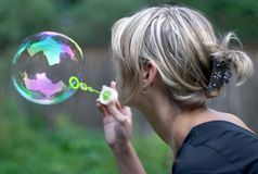 Girl with soap bubble. Young woman playing with soap bubble Royalty Free Stock Photos