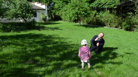 Girl soap bubble hand. Father with a small daughter blowing soap bubbles in the garden. Girl laughing clapping hands stock footage