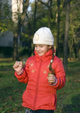 A girl with soap bubbles. Little girl in a red jacket keeps the bubbles Royalty Free Stock Photos