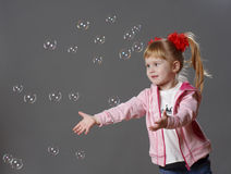 Girl and soap bubbles. Small beautiful girl looking at a soap bubbles Stock Image