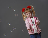Girl and soap bubbles. Small beautiful girl looking at a soap bubbles Stock Photography