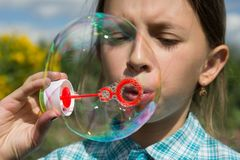 Girl  and soap bubbles 3. A girl in a plaid shirt is playing with soap bubbles. The girl`s eyes are closed. Behind the girl are green grass and yellow flowers Stock Photography