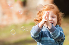 Girl with soap bubbles. Happy girl trying to catch soap bubble stock image