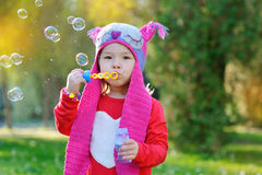 Girl with soap bubbles in a knitted hat handmade Royalty Free Stock Photo