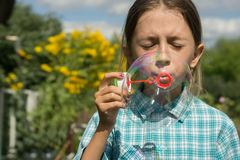 Girl and soap bubbles 1. A girl in a plaid shirt is playing with soap bubbles. The girl`s eyes are closed. Behind the girl are green grass and yellow flowers Stock Image