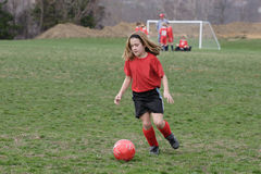 Girl at Soccer Field 16. Girl chasing soccer ball down the field Royalty Free Stock Photography