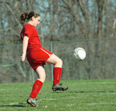 Girl at Soccer Field 20B. Girl kicking ball down soccer field during game Royalty Free Stock Images
