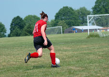 Girl at Soccer Field 27. Girl chasing soccer ball down the field Stock Image