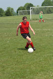 Girl at Soccer Field 28. Girl chasing soccer ball down the field Stock Photography