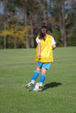 Girl at Soccer Field 40. Girl kicking ball at soccer field during a game Stock Photo