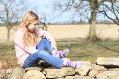 Girl in socks on wall. Sad little kid - hairy blond girl in pink jacket, blue pants taking off socks while sitting on stone wall Stock Images