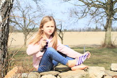 Girl in socks on wall. Sad little kid - hairy blond girl in pink jacket, blue pants taking off socks while sitting on stone wall Royalty Free Stock Photography