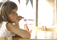 Girl with Soda. Young girl sitting at a table drinking a soda with a straw. Girl is wearing a princess costume and crown. Looking away from the camera Royalty Free Stock Photos