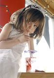 Girl with Soda. Young girl sitting at a table drinking a soda with a straw. Girl is wearing a princess costume and crown. Looking at the camera Royalty Free Stock Photography