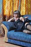 The girl on a sofa in a black peignoir. The girl in a smart interior lies in underwear on a sofa Stock Photo
