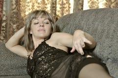 The girl on a sofa in a black peignoir Royalty Free Stock Photos