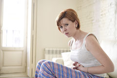 Girl on sofa couch holding hurting belly suffering stomach cramp and period pain Royalty Free Stock Photo