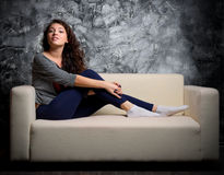 Girl on sofa at dark room Royalty Free Stock Photography