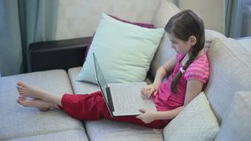 A girl on the sofa is education on a laptop stock footage