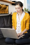 Girl on sofa with laptop, she indicates the displa Stock Photos