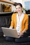 Girl on sofa with laptop, she indicates the displa Royalty Free Stock Photo