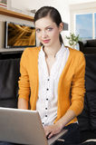 Girl on sofa with laptop, she indicates the displa Stock Photography