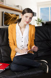 Girl on sofa with laptop, she indicates the displa Royalty Free Stock Image