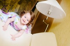 Girl on sofa near lampshade Royalty Free Stock Images