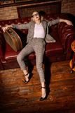 Girl on sofa. Relaxed woman in a elegant suit posing in luxurious vintage interior. Full length portrait. Beauty, fashion royalty free stock images